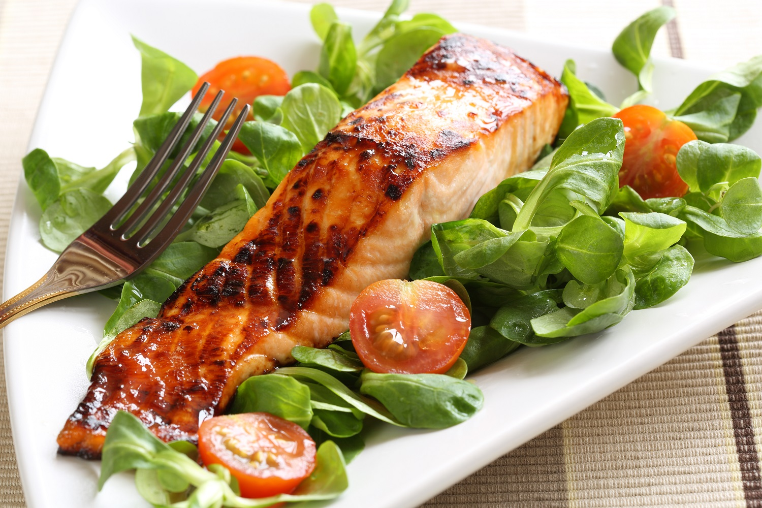 Grilled salmon with a honey glaze on a bed of lambs lettuce